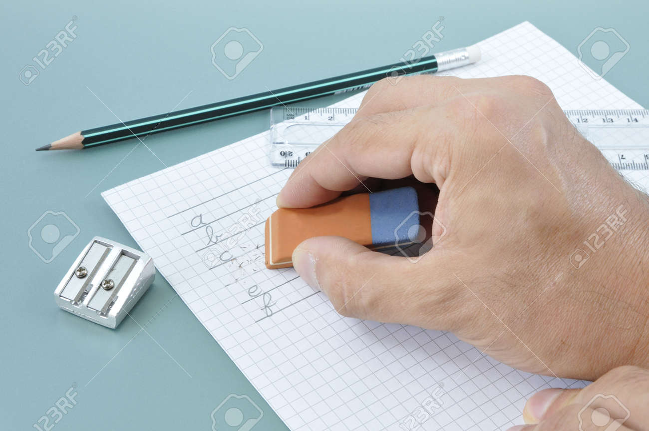 Hand erasing a writed mistake on a white paper during a writing exercise - 7616323