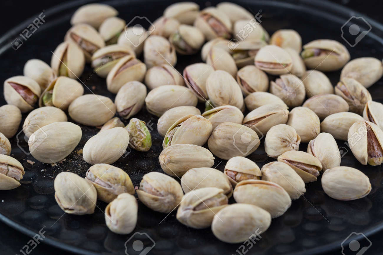 Salted roasted pistachios nuts on old iron background. - 81495492