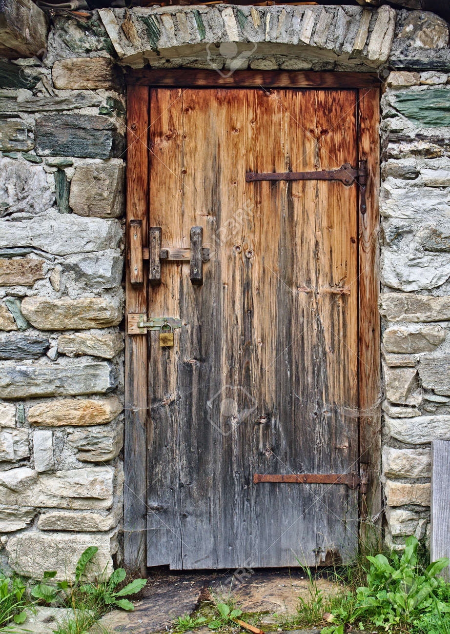Old Wooden Door In Field Stone Wall With Big Rusty Hinges And Stock Photo Picture And Royalty Free Image Image 85102776