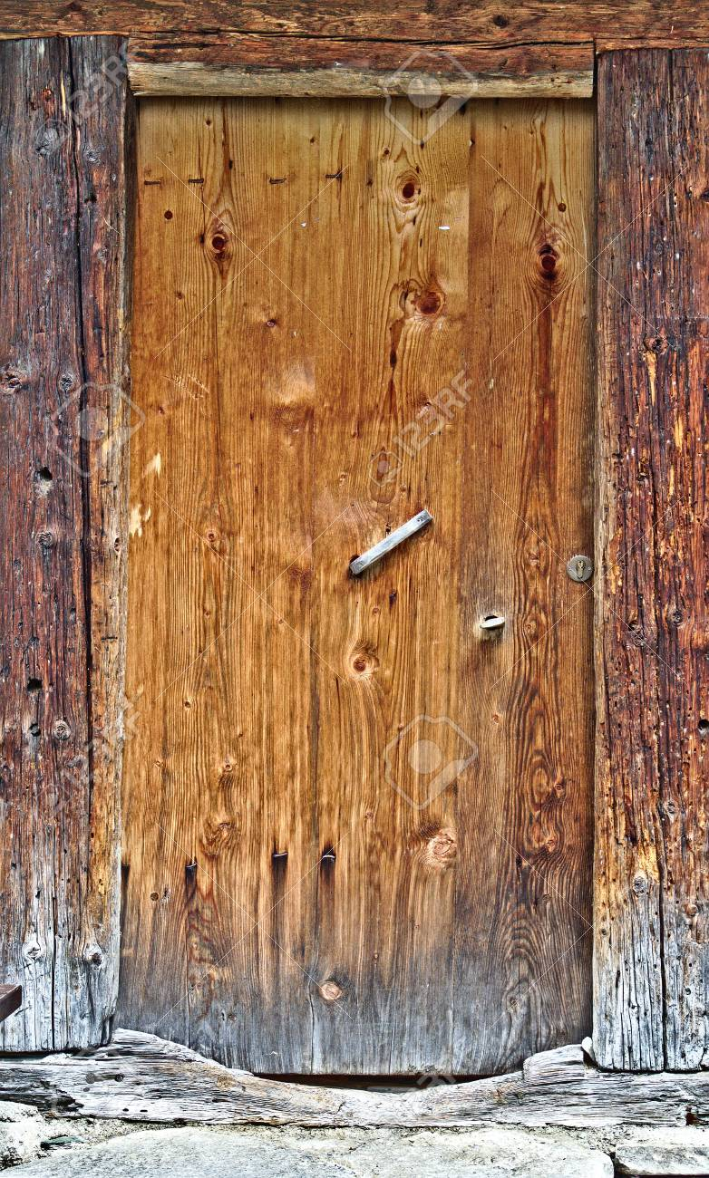 Old Wooden Door With Big Cracked Wooden Door Frame Stock Photo
