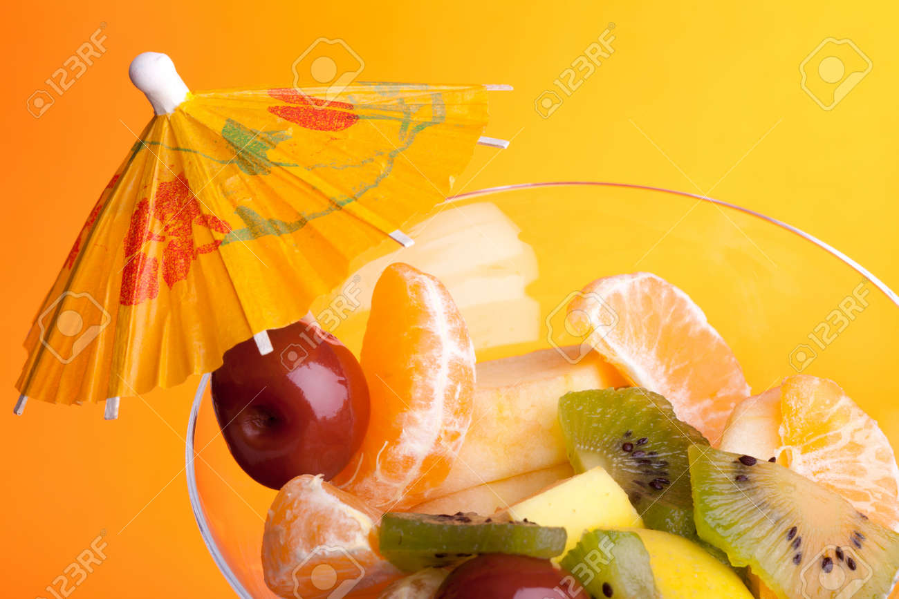Food - Desserts - Cup with fruit salad decorated with paper umbrella, isolated on orange background. Stock Photo - 8678426