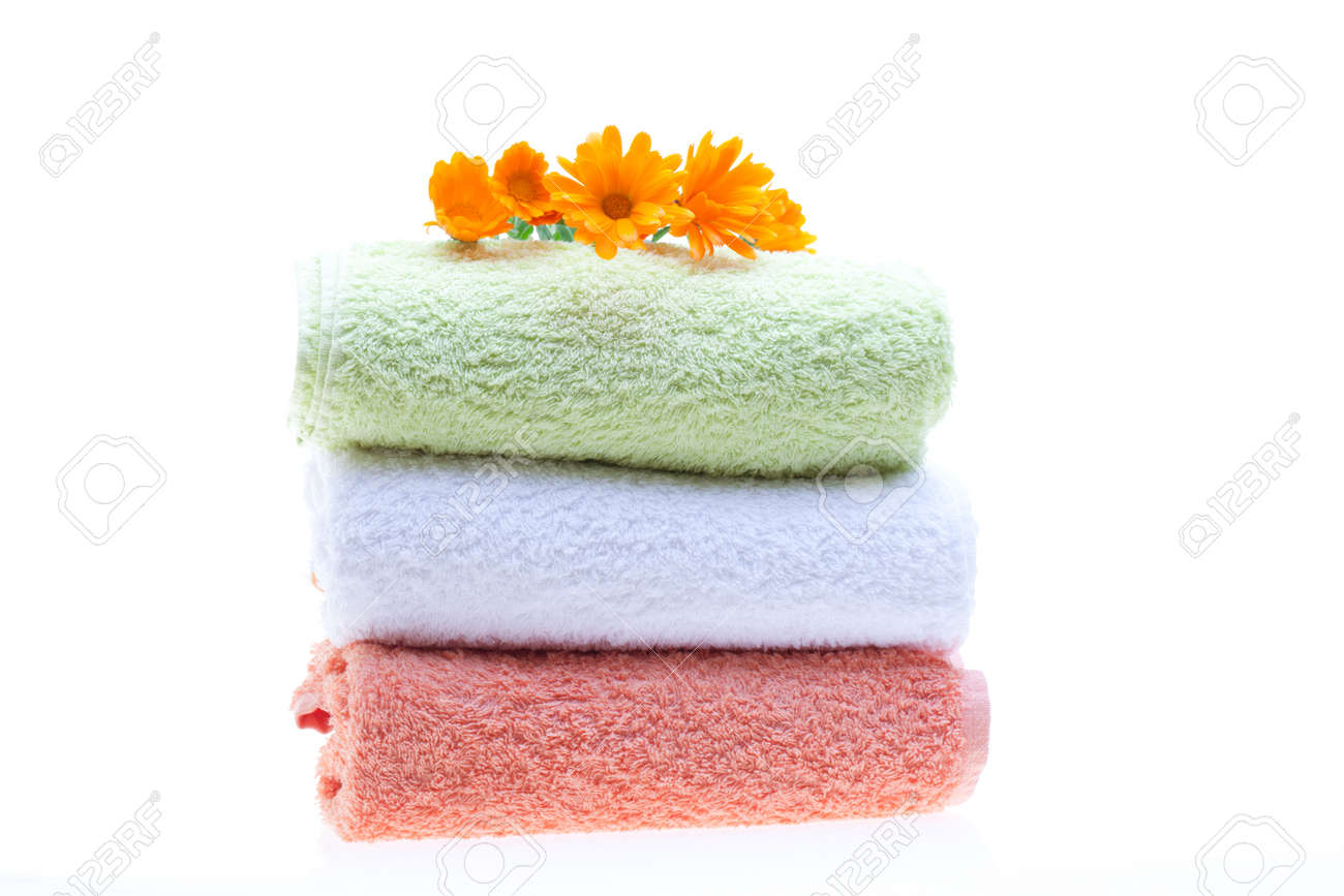 Pile of towels with calendula flowers on top, isolated on white background. Stock Photo - 13354416