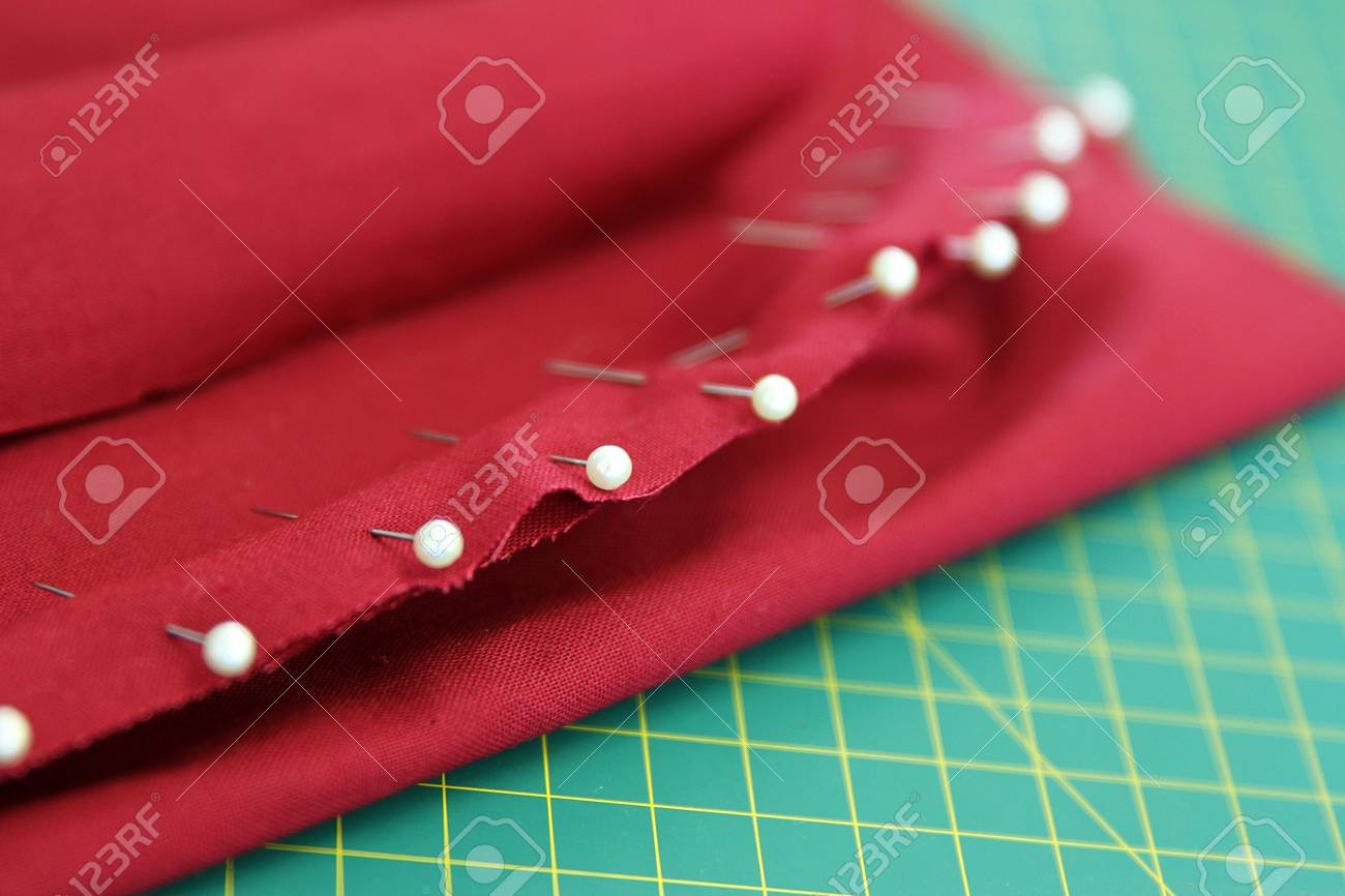 haberdashery  white pearl head pins in a piece of material fabric