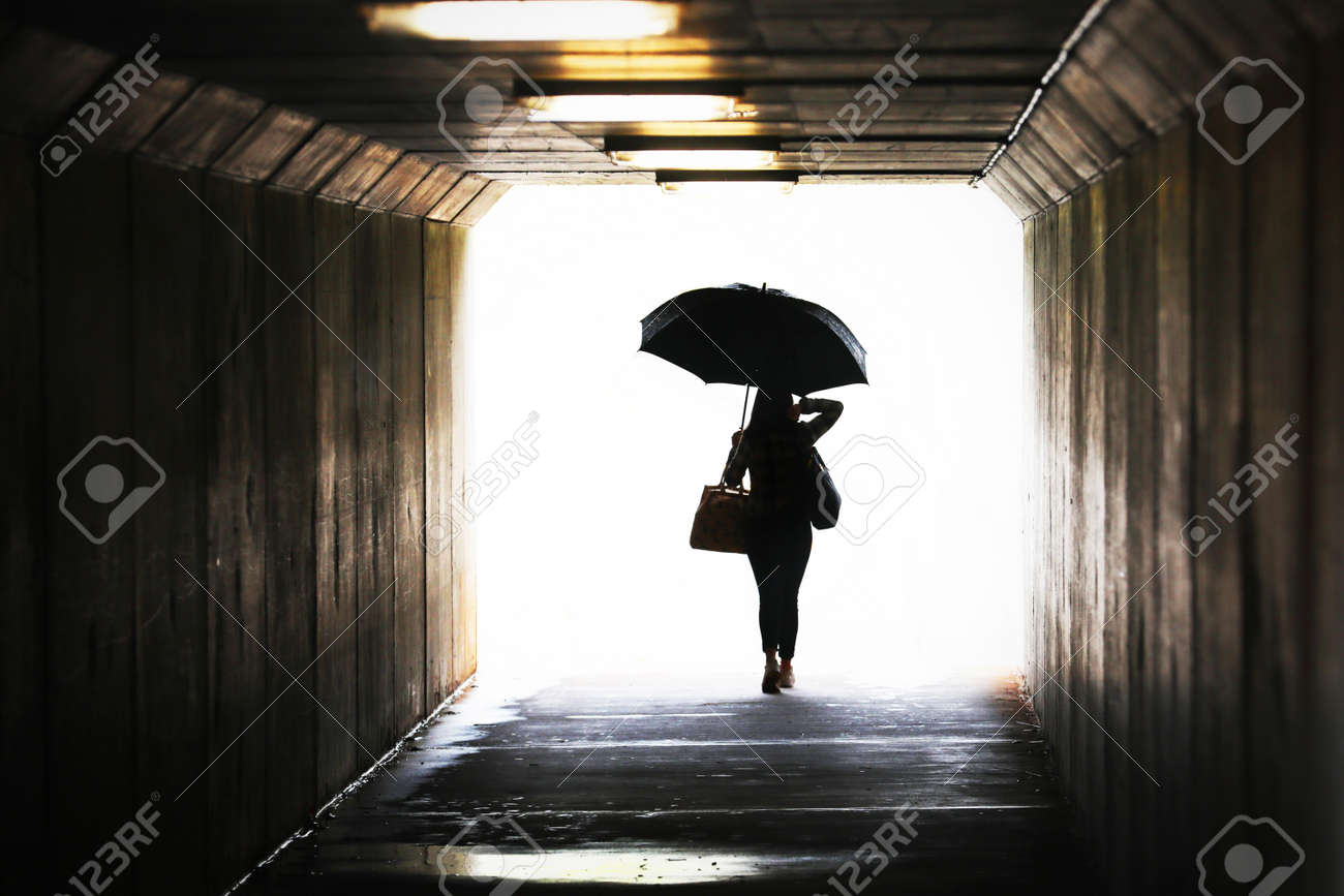 Highly saturated silhouette of a confident woman holding an umbrella exiting a tunnel. Wet weather working city chic lifestyle. Weather forecast, rain and showers. Leaving arriving confidence concept - 154934037