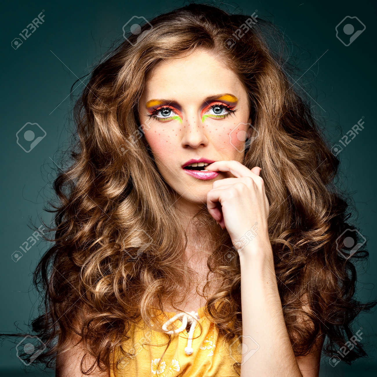 a studio portrait of a young woman with long, blonde and wavy hair and blue eyes. her make-up is very colorful; it is inspired by the '60s style and she has freckles drawn on her cheeks. she has one hand up to her face and one finger in her mouth, which g Stock Photo - 8259373