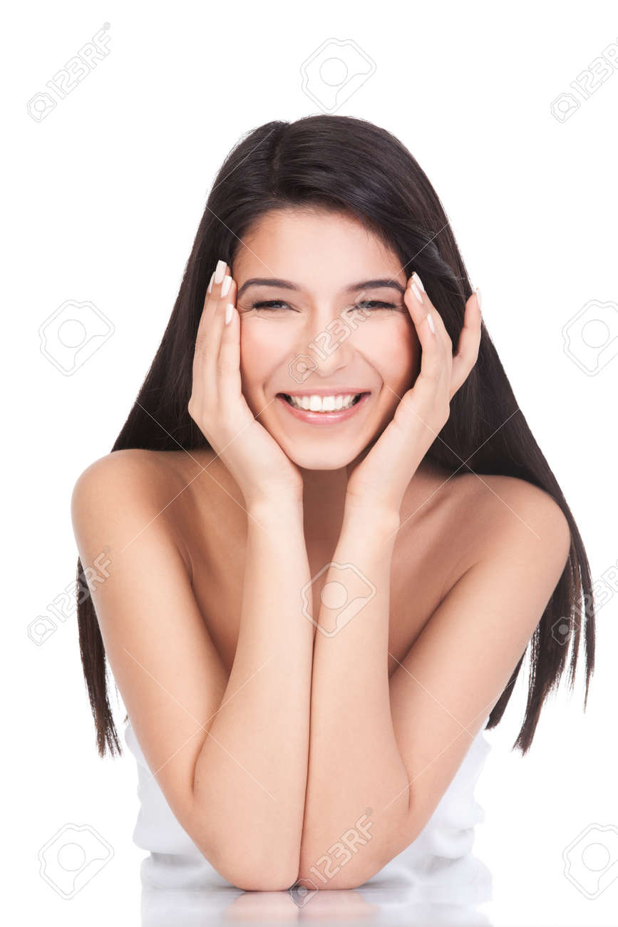 a portrait of a young woman, posing on a white background. she has both her elbows resting on a white table. both her hands are on her face, she has a wide smile and a relaxed face expression. Stock Photo - 8333445