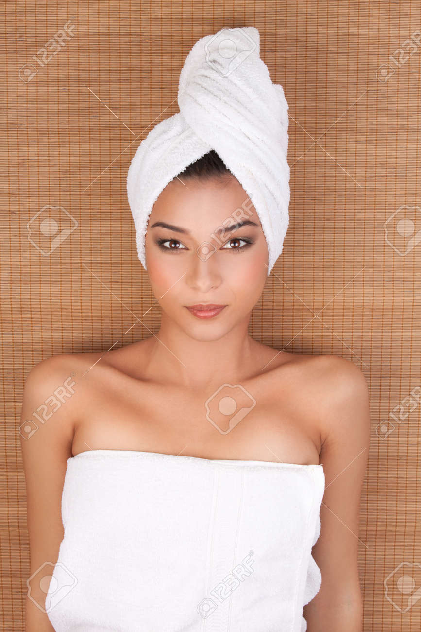 a portrait of a young woman at a day spa, layed on her back, on a mat, with her hair and body wrapped in white towels. Stock Photo - 8333447