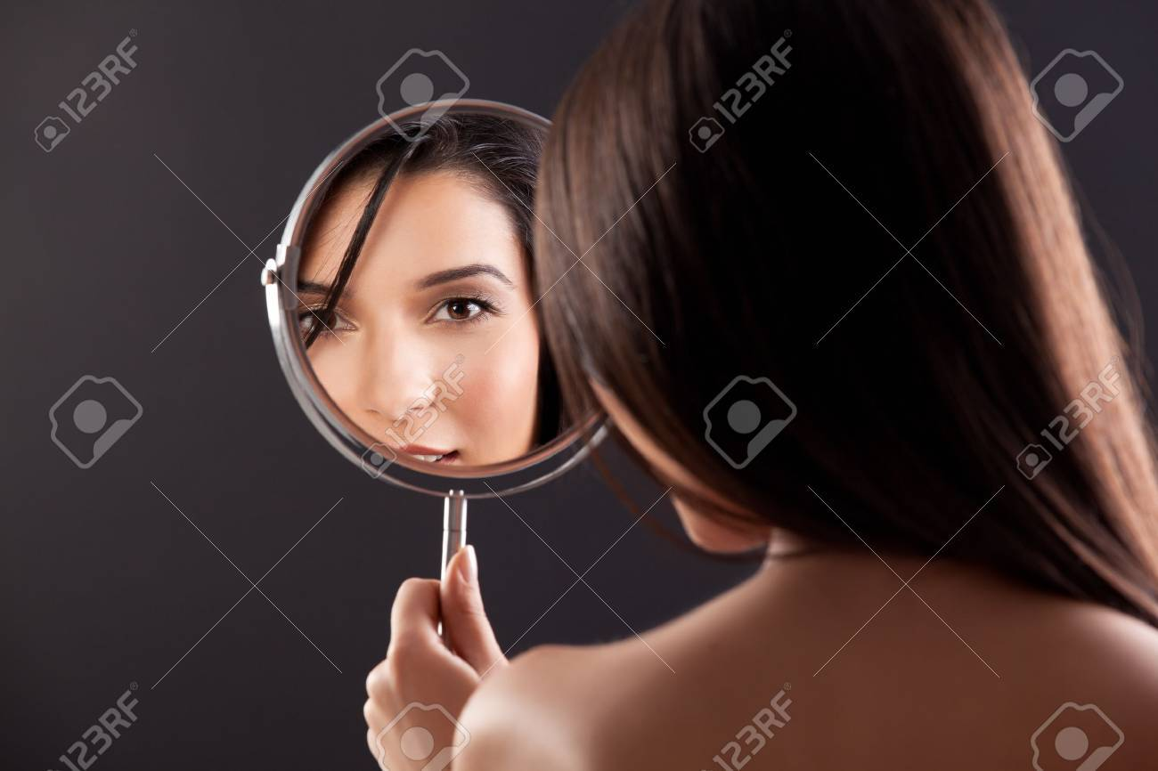 a beauty studio picture of a young woman looking in a mirror, while her back is turned to the camera. the mirror held over her left shoulder reflects her smiling face. Stock Photo - 8991363