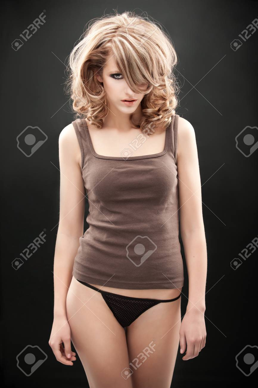 a beauty portrait of a young, blonde woman, wearing a 1960's make-up and hairstyle and a brown top with black underwear Stock Photo - 9169835