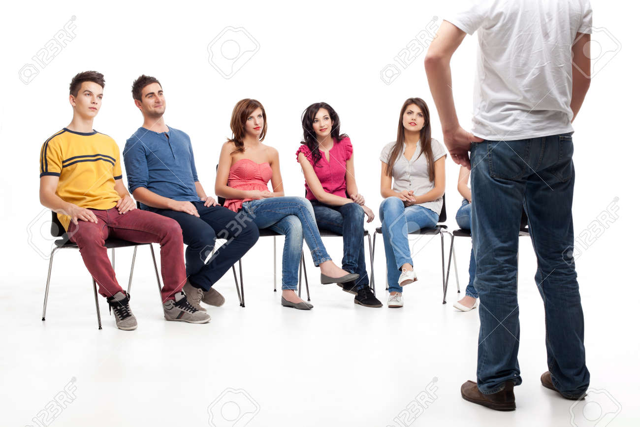 young group of friends, sitting down, listening to man standing Stock Photo - 9937523