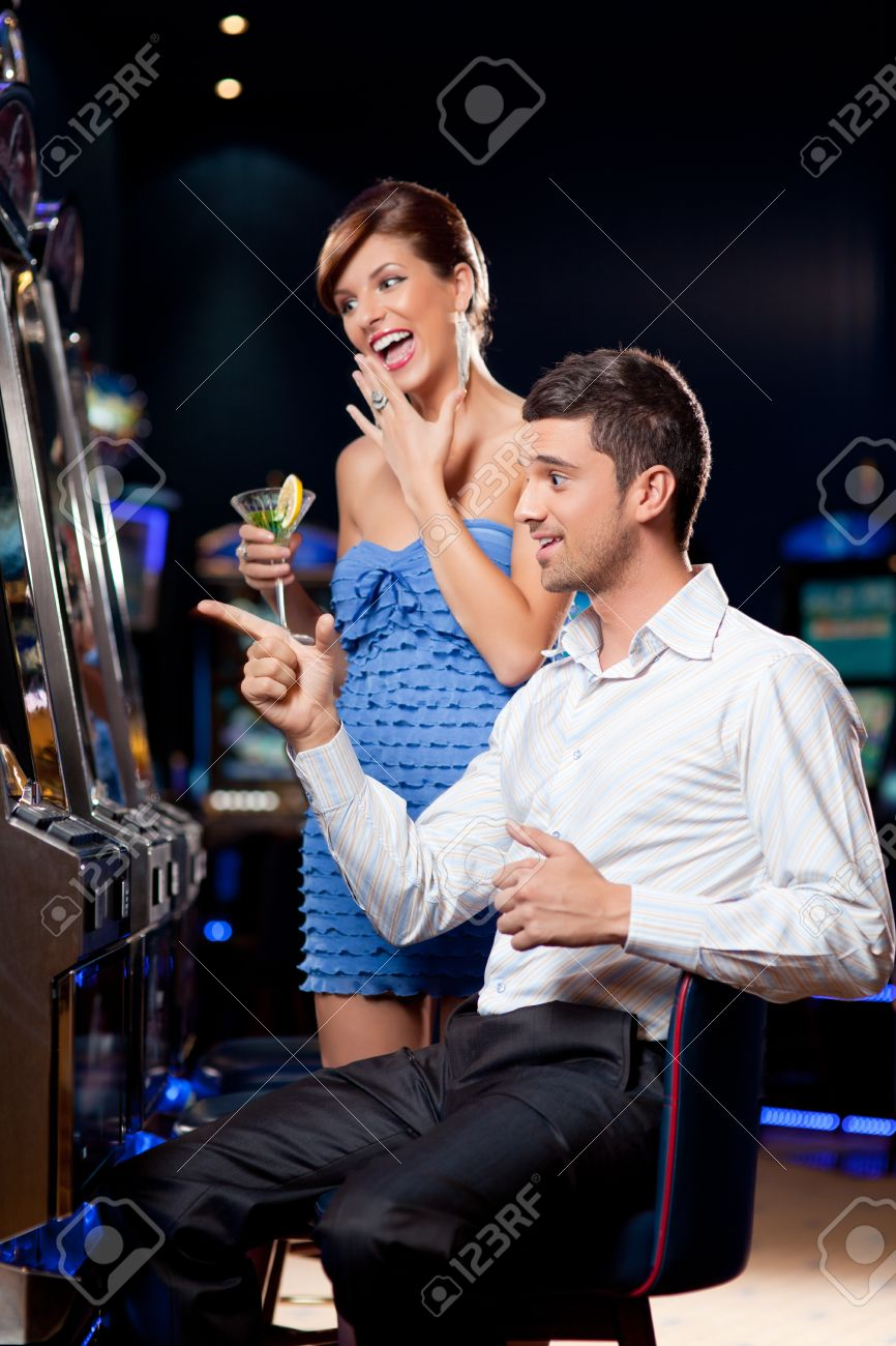 young couple watching exiting, winning at the slot machine Stock Photo - 10298308