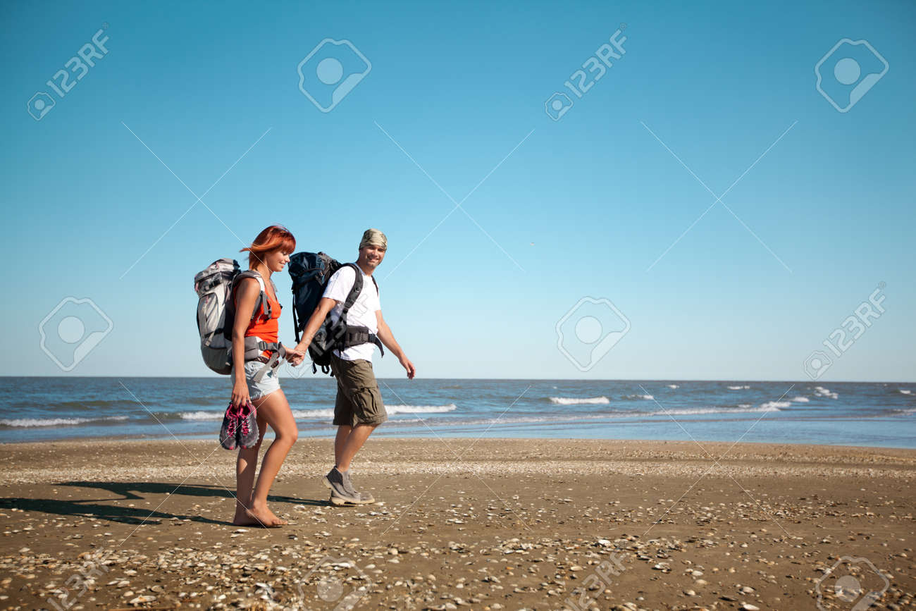 happy, young couple walking together on a deserted beach, wearing backpacks Stock Photo - 11532563