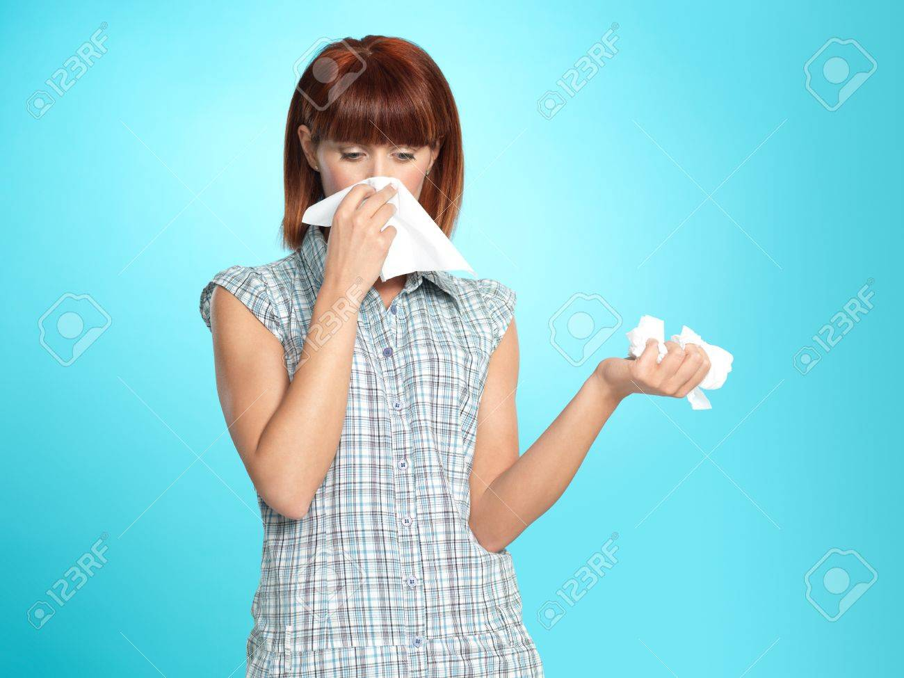 beautiful young woman, crying, blowing her nose, on blue background Stock Photo - 13239939