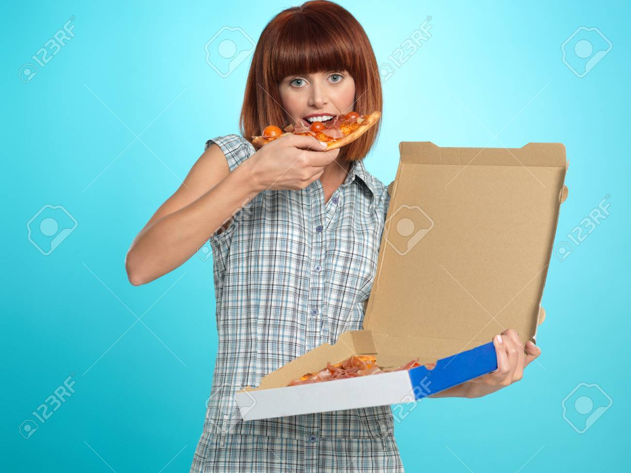 beautiful young woman, eating a pizza pie from the delivery box, smiling, on blue background Stock Photo - 13240299