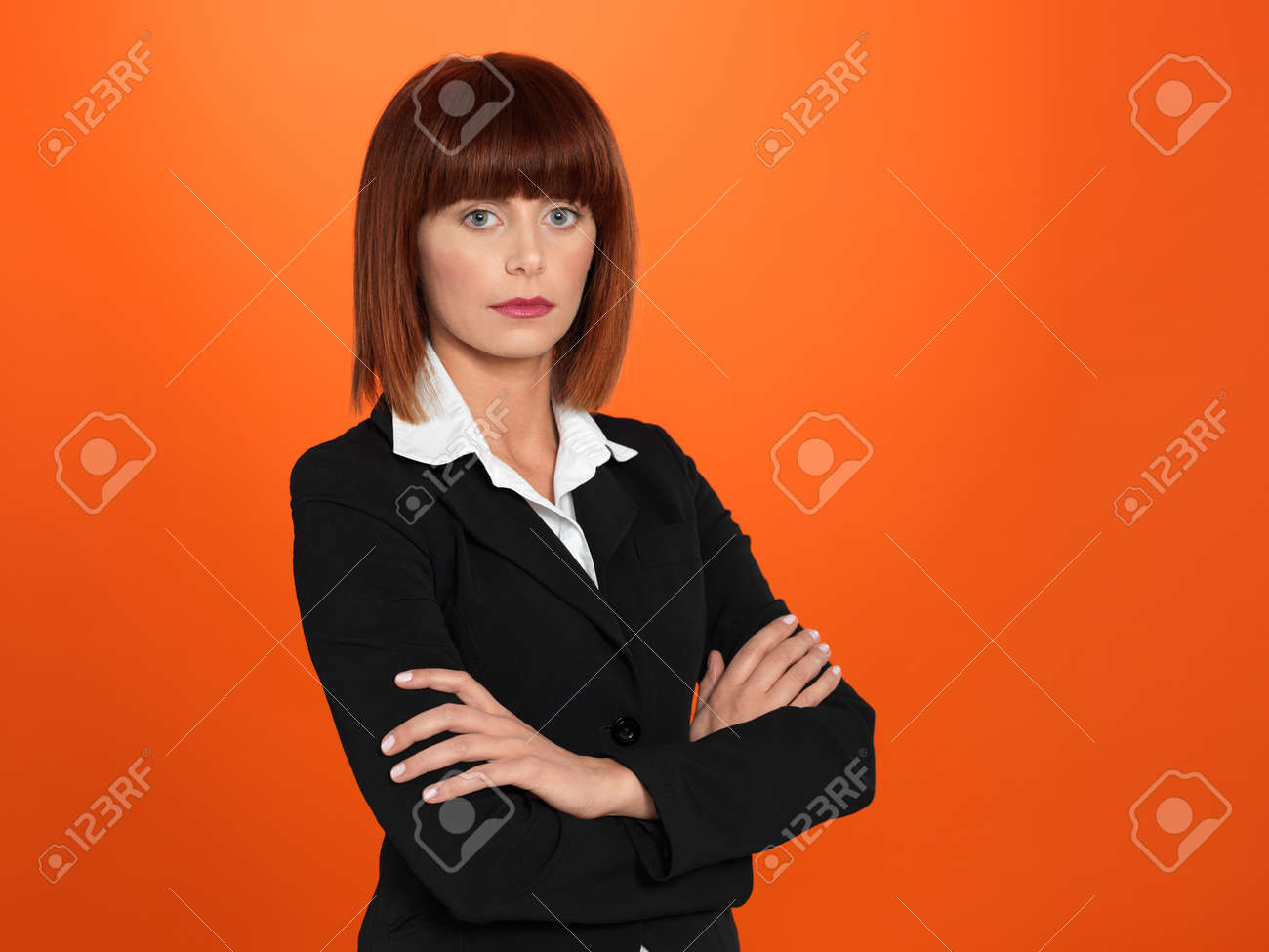 portrait of a beautiful, young, businesswoman, with her arms crossed, on orange background Stock Photo - 13239439
