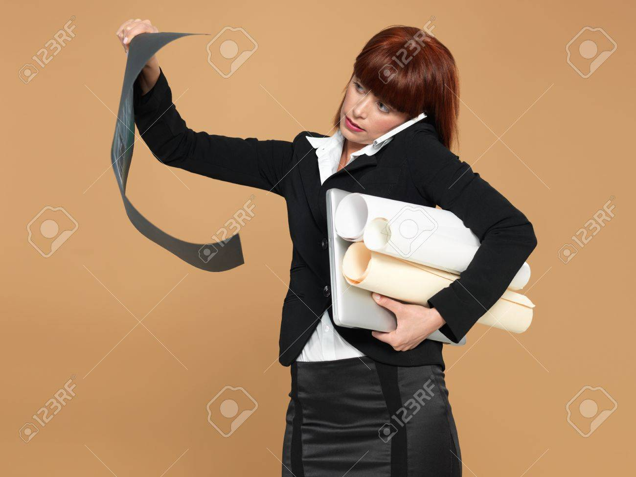 portrait of a bussy, young woman architect, holding a laptop and a blueprint, talking on the telephone, on beige background Stock Photo - 13239358
