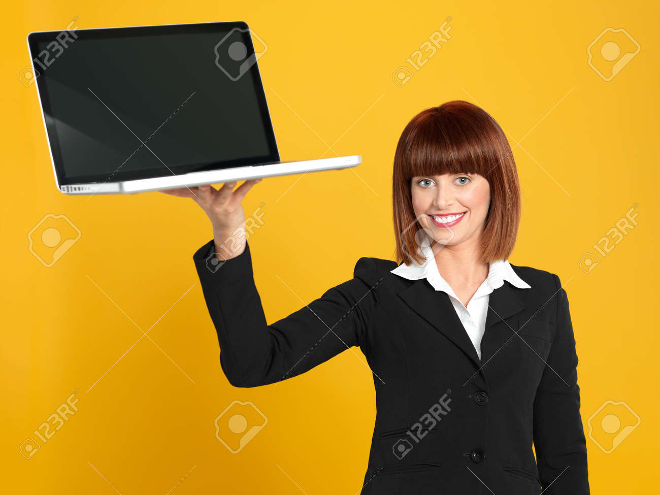 funny portrait of a beautiful, young businesswoman, holding a laptop as a tray, smiling, on yellow background Stock Photo - 13239381