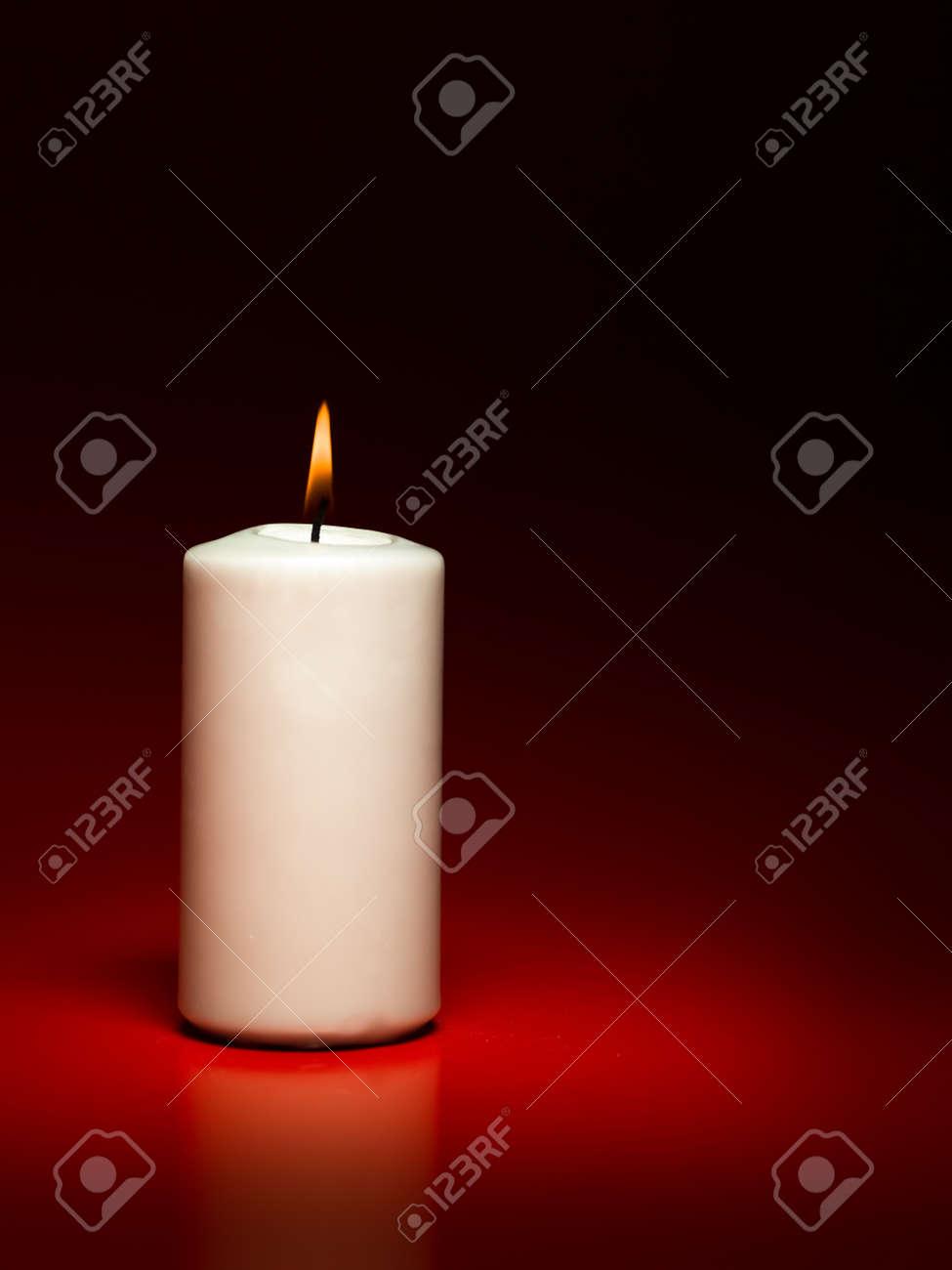 closeup of single white burning candle on red background Stock Photo - 16775076