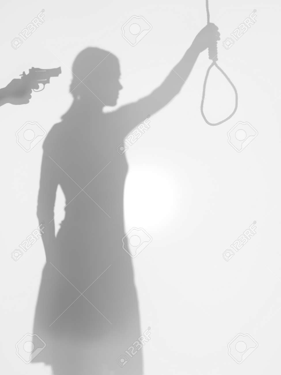 female body silhouette holding a strangling rope while beeing threatened with a gun, behind a diffuse surface Stock Photo - 17884496