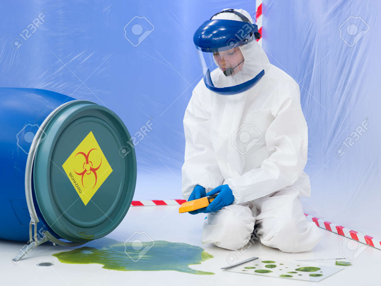 close-up of female scientist wearing white protection suit and mask, measuring the level of contamination at  a biohazard accident Stock Photo - 20691444