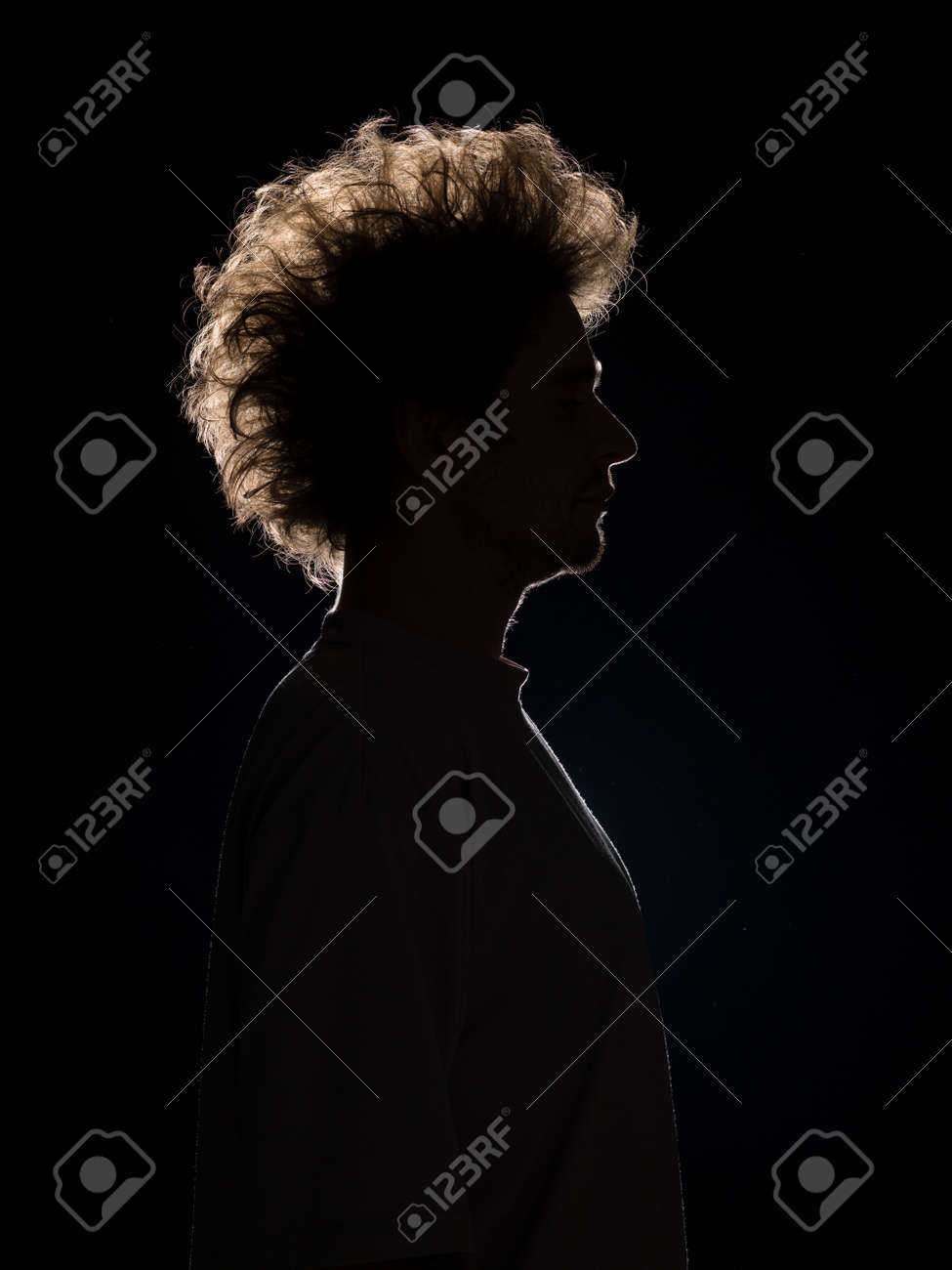 Profile of man in black shadow with tousled hair on black background stock photo 23926870