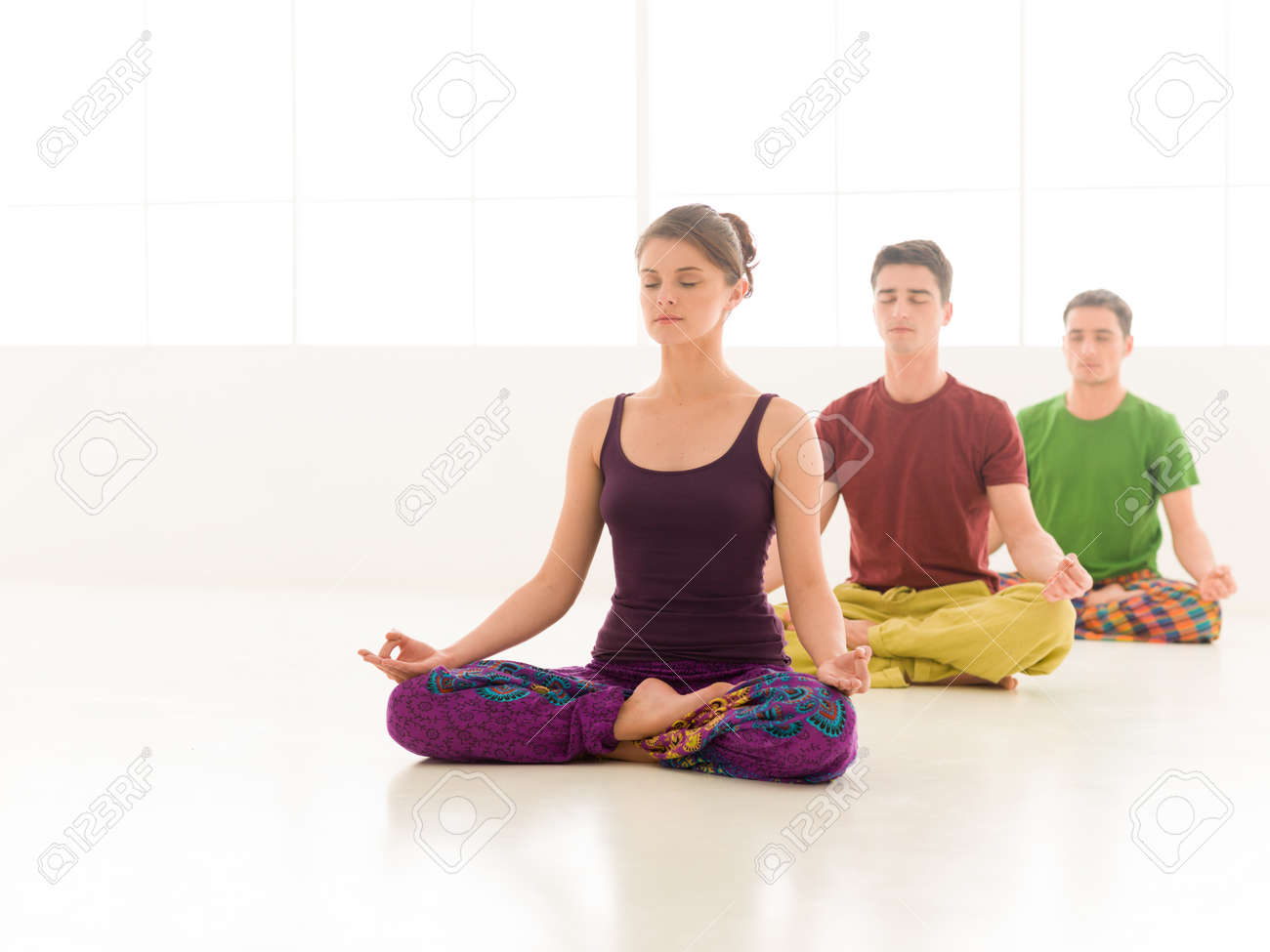 Three Young People A Woman And Two Men Practice Yoga Class Stand