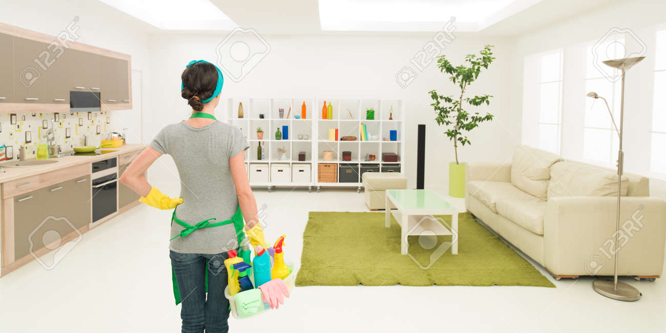 Young Caucasian Woman Standing In Clean House Holding Cleaning Products,  Looking At Tidy Room Stock