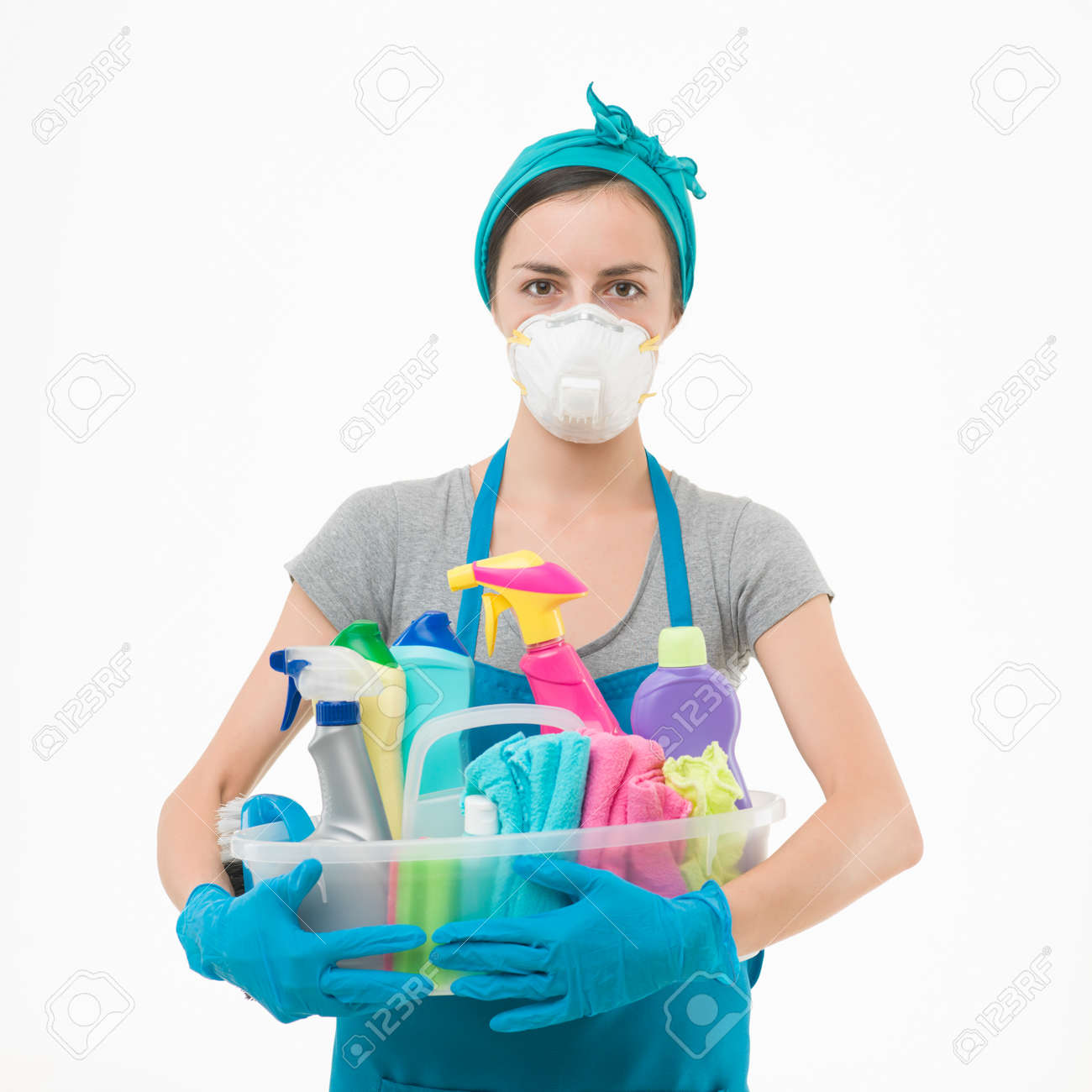 young housewife wearing protection mask, holding cleaning supplies against white background - 36919998