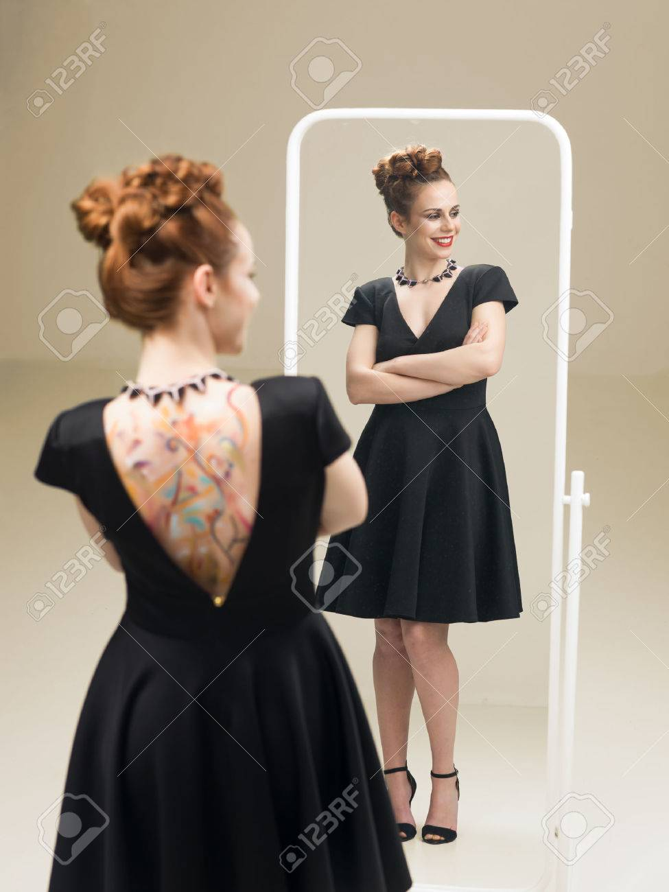 1fd982f6cac beautiful red headed woman in fancy black dress standing in front of mirror  looking happy Stock