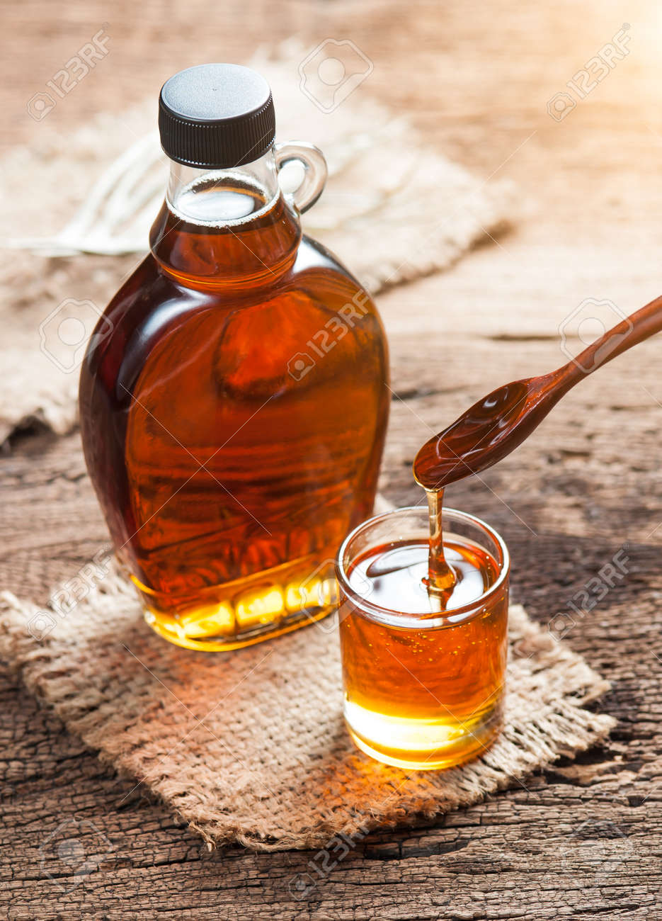 7a39ce783b1 maple syrup in glass bottle on wooden table Stock Photo - 48842222