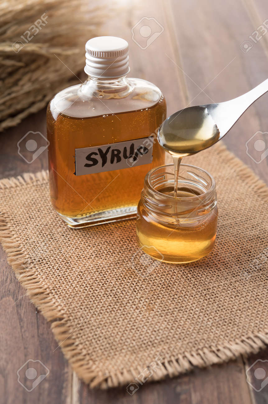 dc31d5486ad Glass bottle of syrup with spoon on wooden background Stock Photo - 99207409