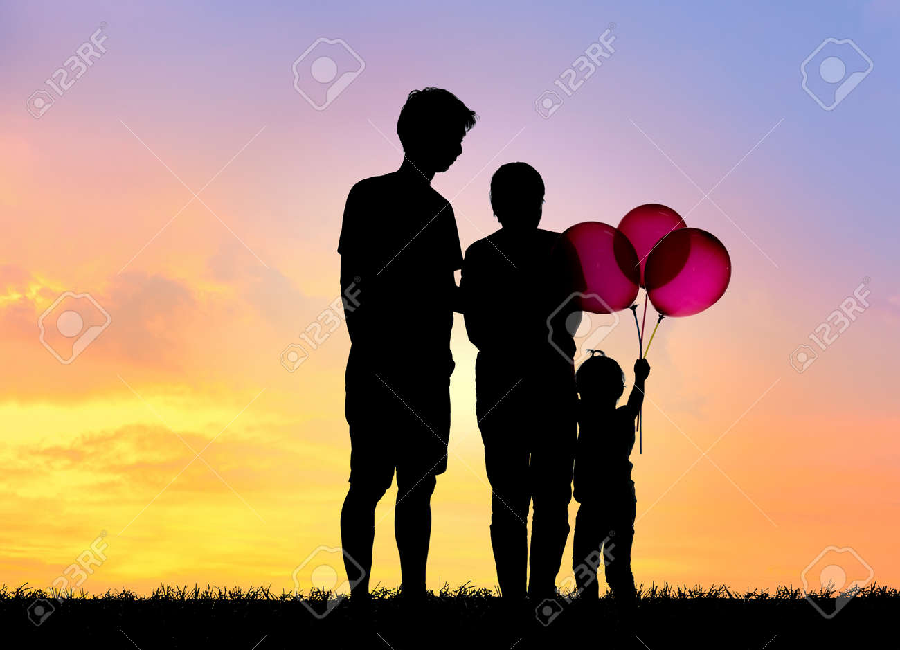 Silhouette family,father, mother and children holding balls against the sunset. - 137522969