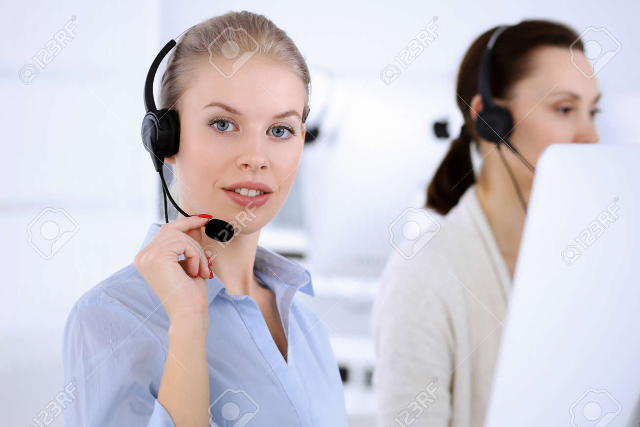 Call center office. Beautiful blonde woman using computer and headset for consulting clients online. Group of operators working as customer service occupation. Business people concept - 131051433