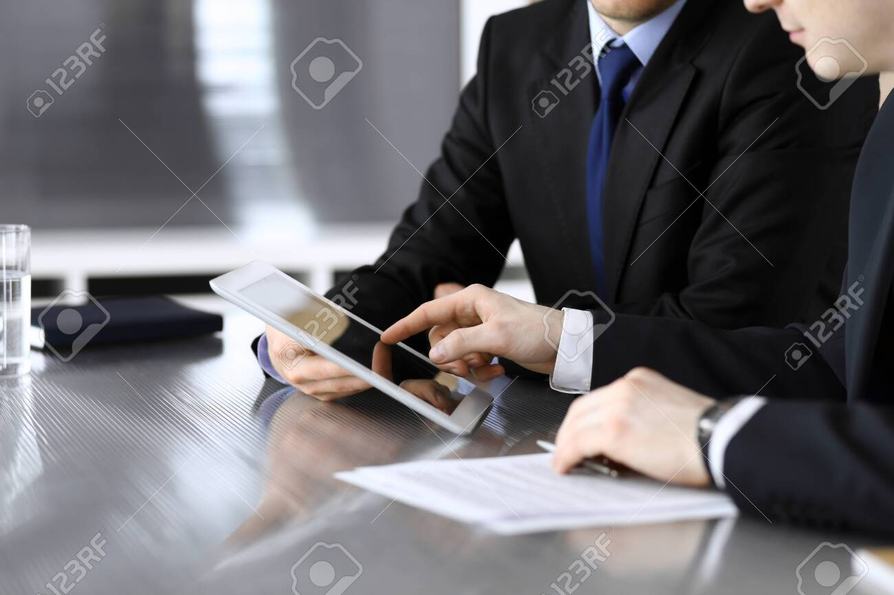 Businessman using tablet computer and work together with his colleague or partner at the glass desk in modern office, close-up. Unknown business people at meeting. Teamwork and partnership concept. - 133114011