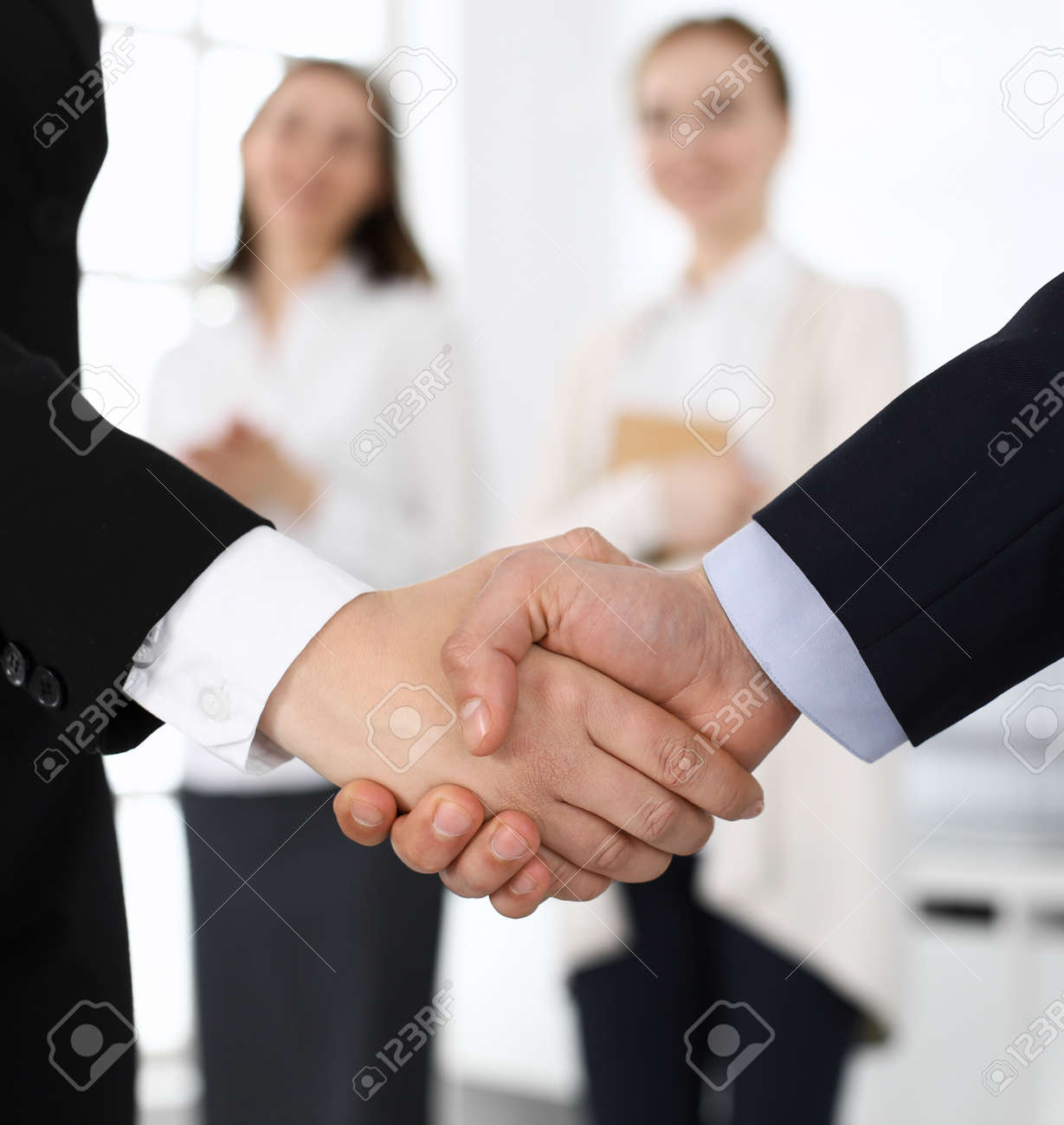Businessman and woman shaking hands with colleagues at the background. Handshake at meeting in office. Concept of success in business - 155595899