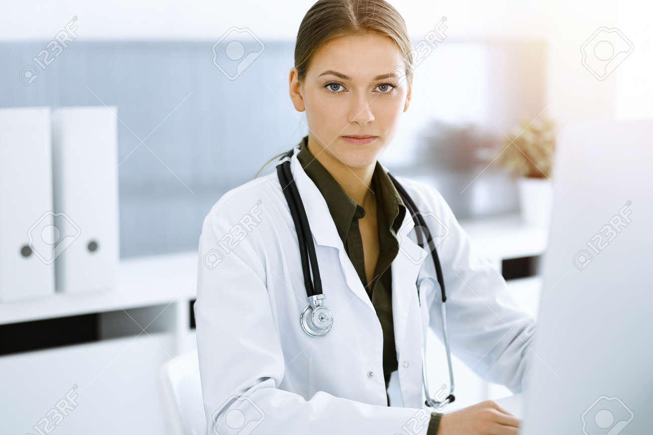 Woman-doctor typing on pc computer while sitting in sunny hospital office. Data in medicine and healthcare - 165697716