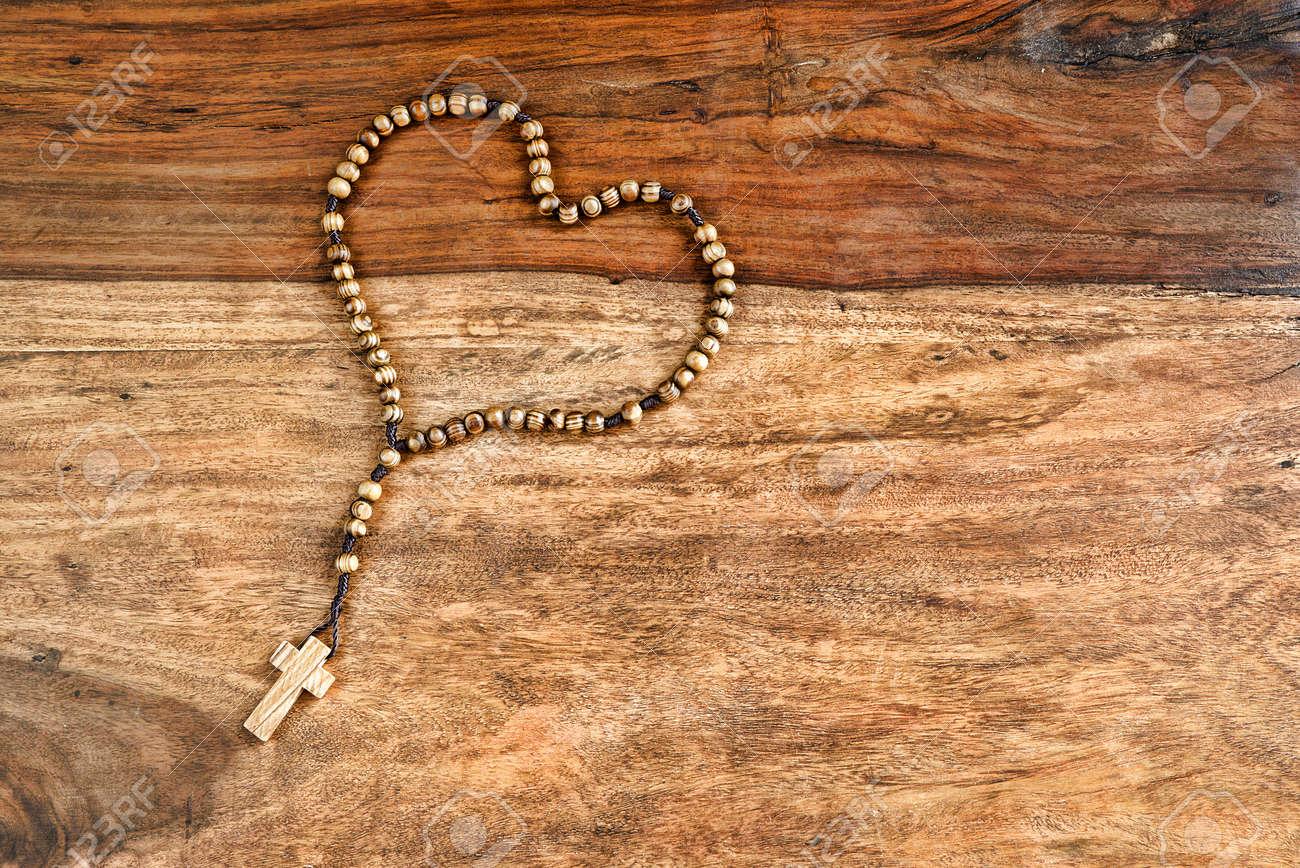 075cdcc3ce5 Una Cruz De Madera De Olivo Con Cuentas Simples O Rosario Descansa Sobre  Una Mesa Rústica Se Establece En La Forma De Un Corazón.