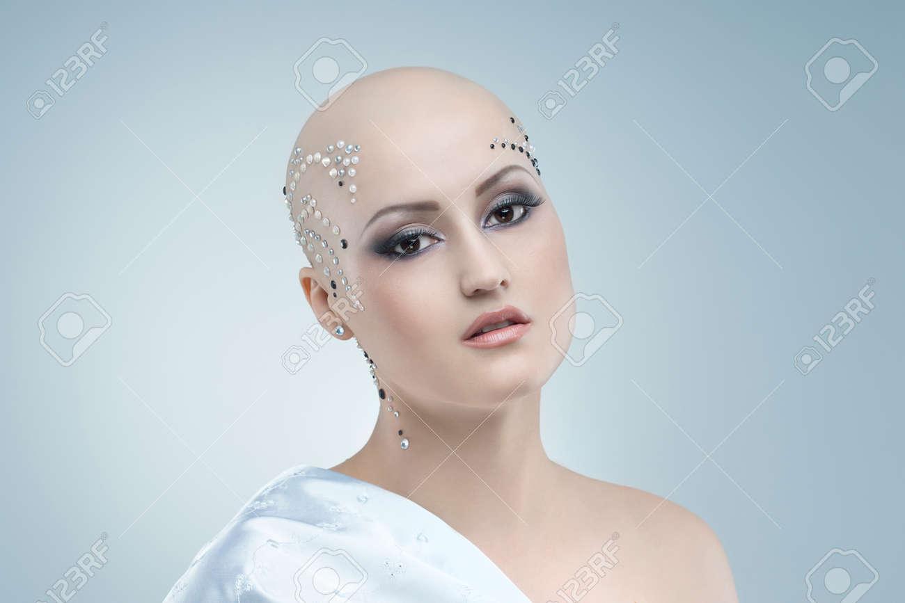 studio portrait of a beauty bald girl on a sky blue background