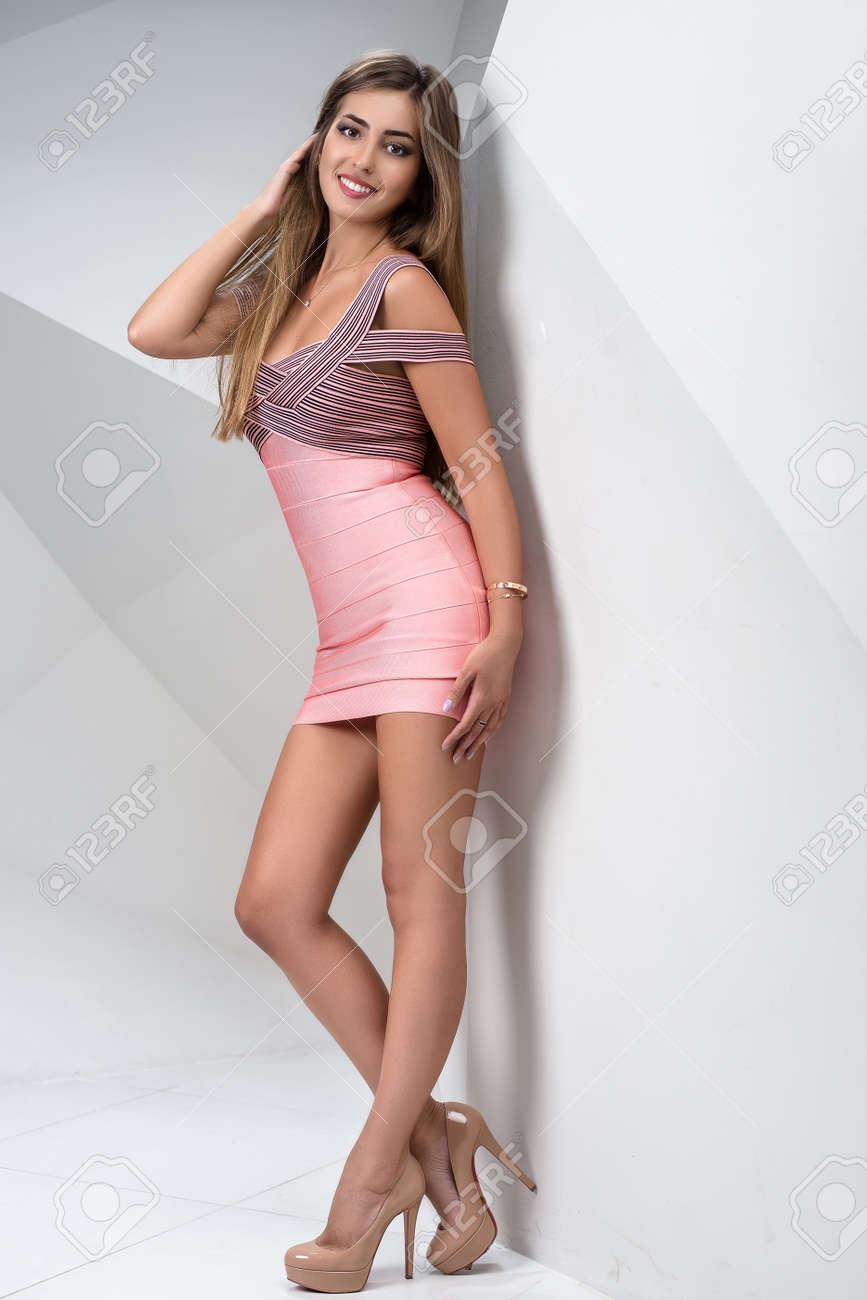 096846e56 Foto de archivo - Hermosa chica elegante posando en un estudio interior.  Una niña está de pie junto a un blanco moderno