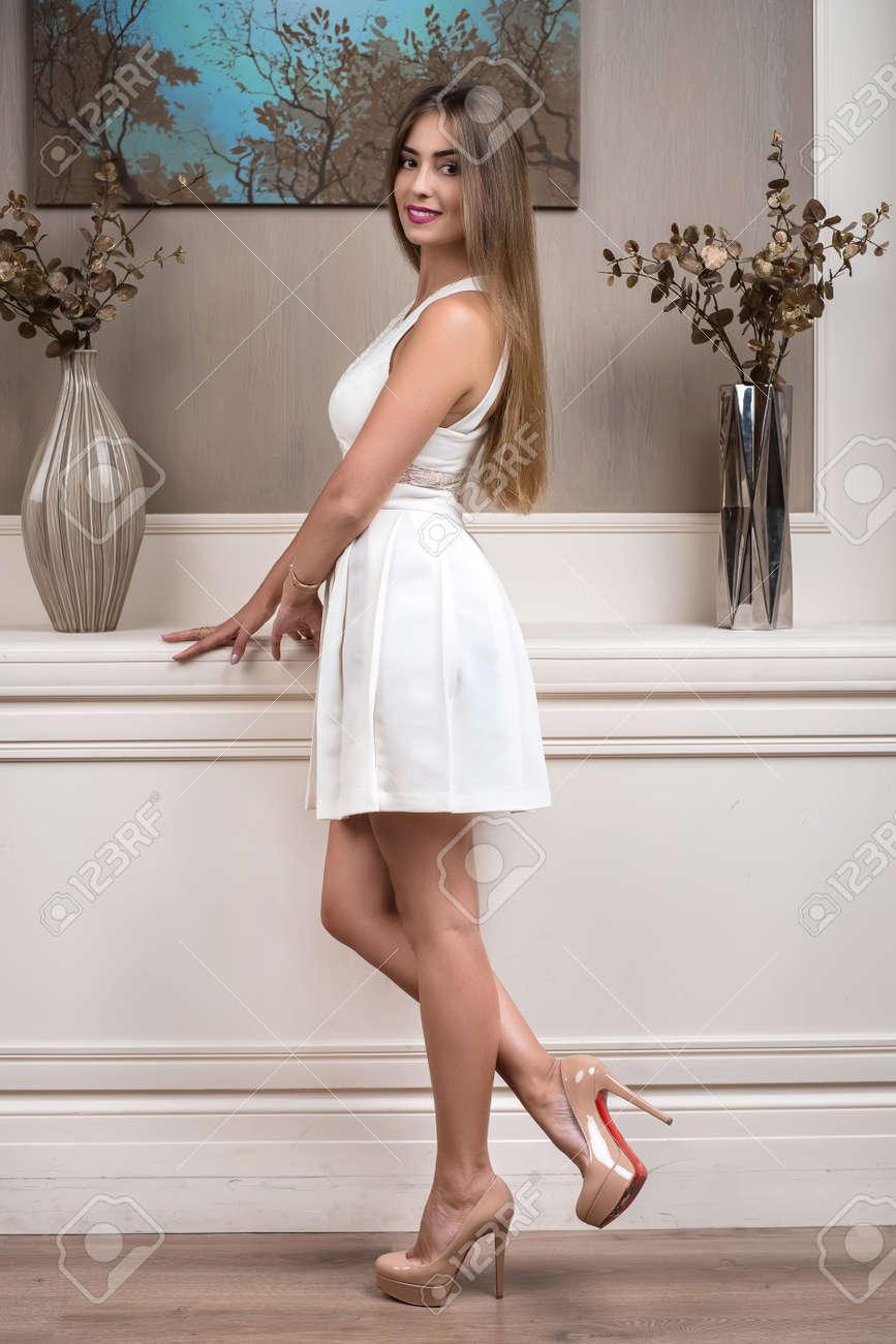 916afef51 Foto de archivo - Hermosa chica elegante posando en un estudio interior.  Una niña está de pie junto a una pared moderna y decorada. Foto de moda.