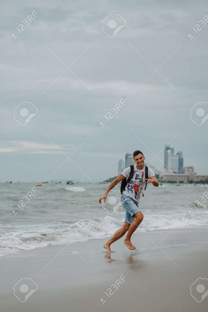 Young man enjoying his vacation on the ocean coast. Running, jumping and having fun at the seaside. Fun on the ocean. Evening Pattaya, Thailand. - 120644956