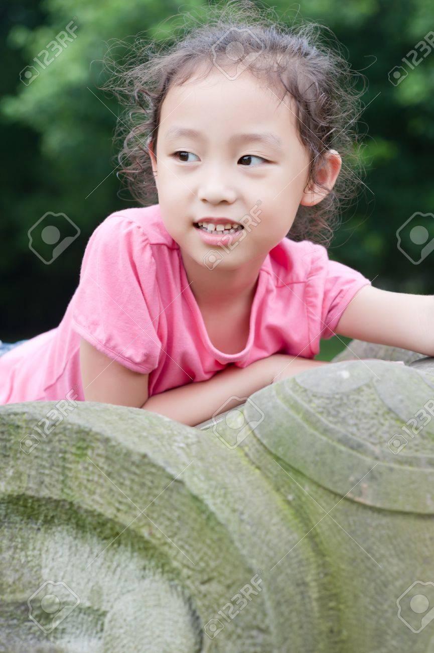 cute little asian girl sit on Stone elephant Stock Photo - 7894170