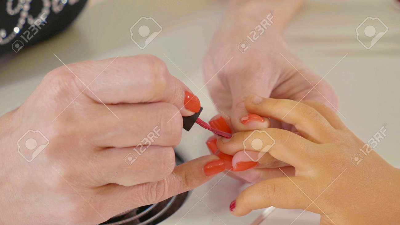 Closeup Shot Of A Beautician Applying Nail Polish To Kids Nail ...