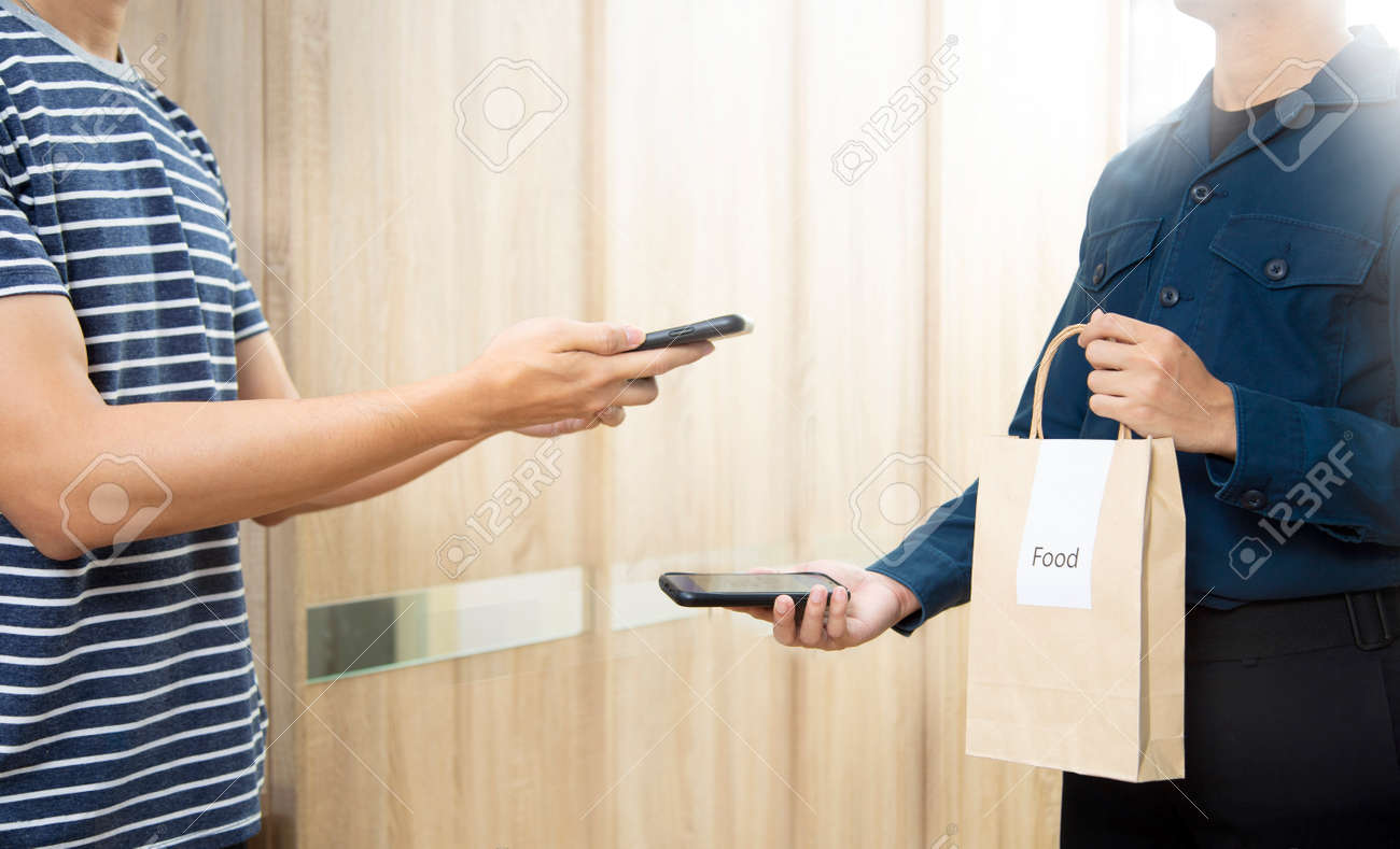 Man recieve food in paper bag delivery using smartphone scan payment digital wallet. - 141046970