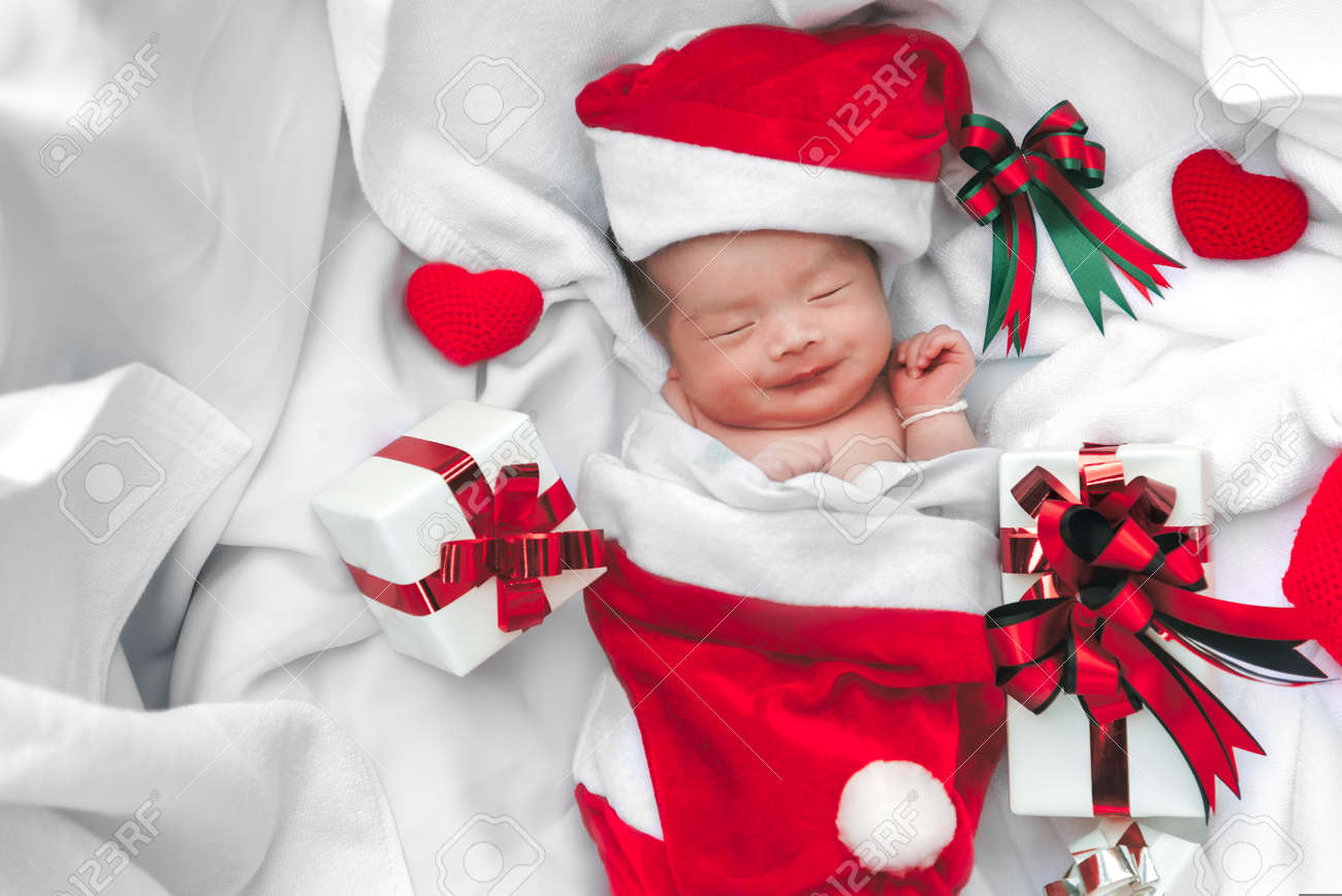 Sleeping newborn baby face in christmas hat with gift box from santa claus and yarn heart on white soft towel cute infant lifestyle and innocent happy baby