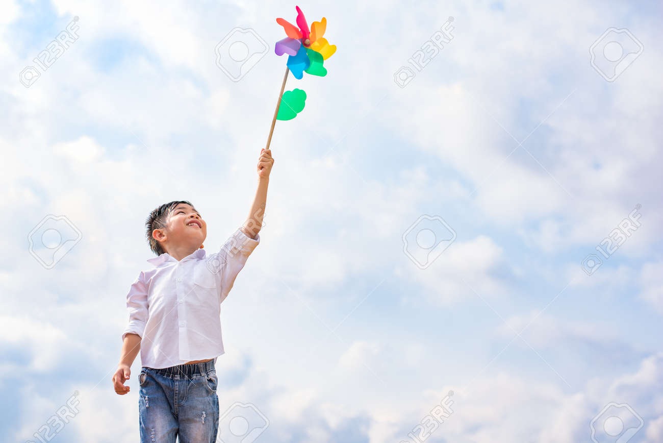 Boy holding colorful pinwheel in windy at outdoors. Children portrait and kids playing theme. - 125033093