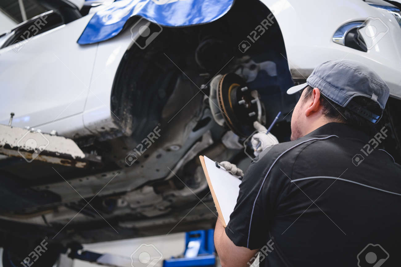 Asian male car technician car maintenance for customers according to specified vehicle maintenance checklist. Disk brake pad wear automotive repairing on vehicle. Safety inspection check service - 129403205