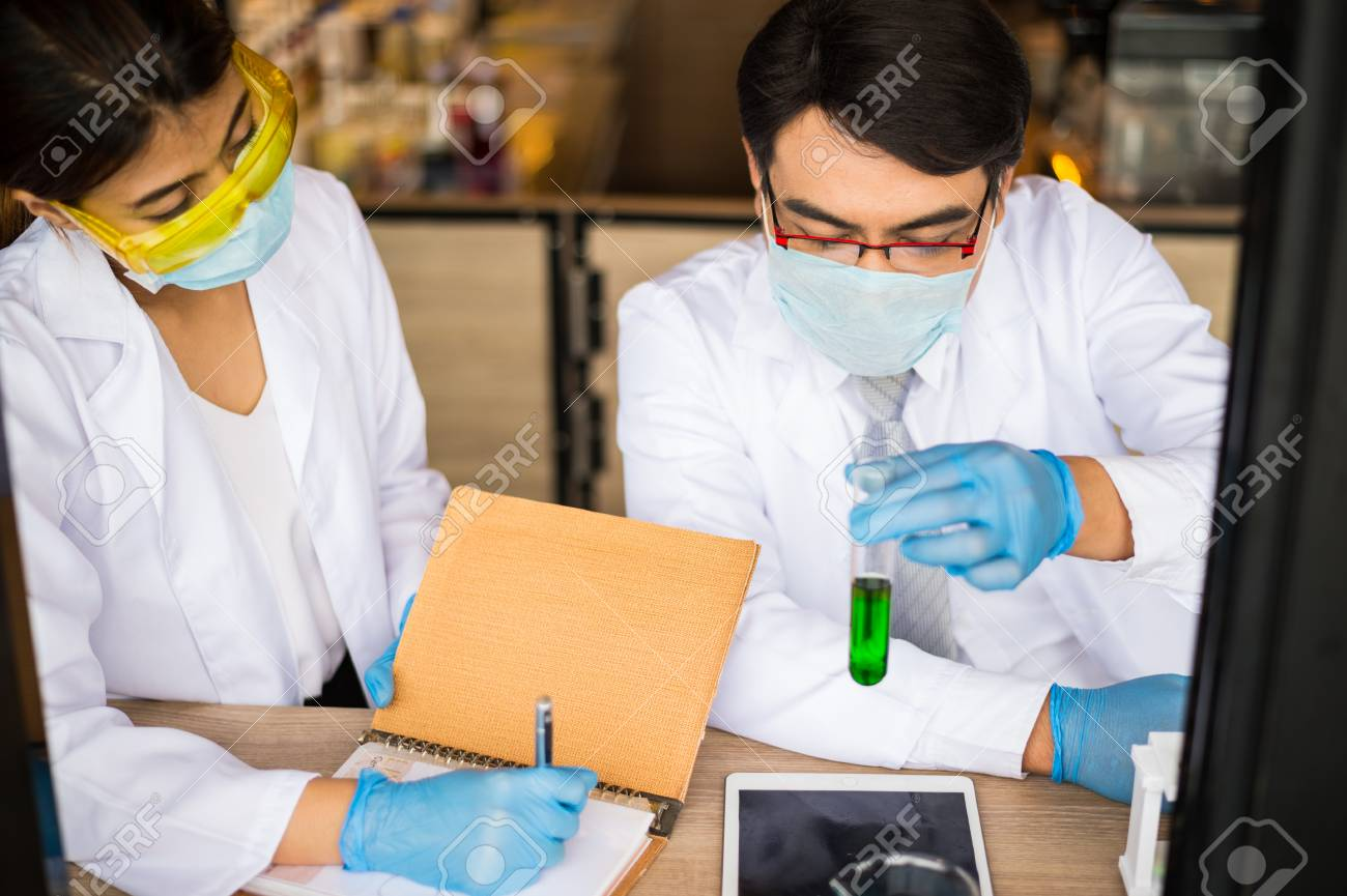 9ca854388028 scientist man holding glass test tube and scientist woman write on notebook.  Chemist examines chemical