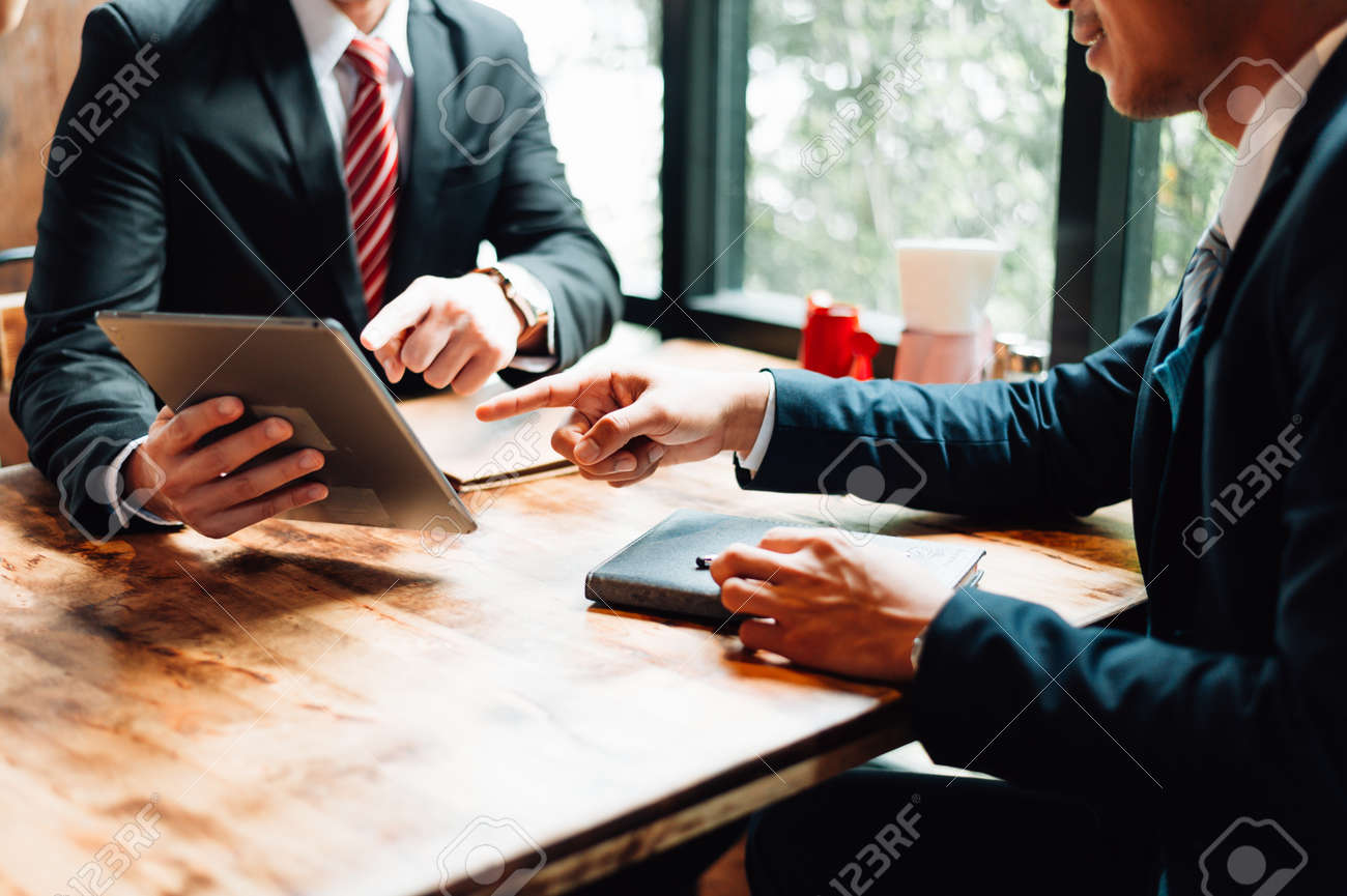 two businessman sitting and looking at tablet, they are meeting about business plan, marketing and financial in the future. concept of business success, business meeting. - 110119189