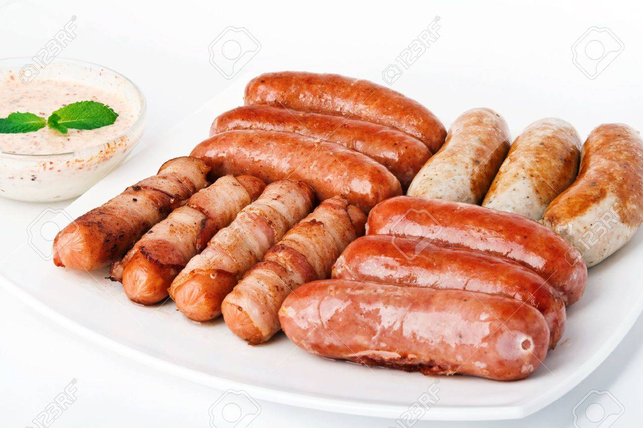 Grilled sausages with sause on white plate - 9898149